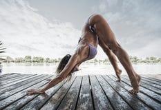 Dorosła kobieta robi joga w bikini na drewnianej rzecznej tratwie Zdjęcie Stock