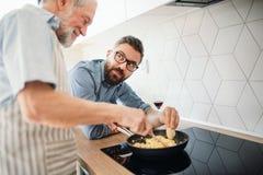 Doros?y modnisia syn indoors i starszy ojciec w kuchni w domu, gotuj?cy obrazy royalty free