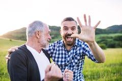 Dorosły modnisia syn z starszym ojcem na spacerze w naturze przy zmierzchem Obraz Royalty Free