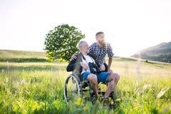 Dorosły modnisia syn z starszym ojcem w wózku inwalidzkim na spacerze w naturze przy zmierzchem Obraz Royalty Free
