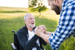 Dorosły modnisia syn z starszym ojcem w wózku inwalidzkim na spacerze w naturze przy zmierzchem Obraz Stock