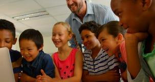 Dorosli Kaukascy męskiego nauczyciela nauczania dzieciaki na laptopie w sali lekcyjnej przy szkołą 4k zbiory