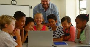 Dorosli Kaukascy m?skiego nauczyciela nauczania dzieciaki na laptopie w sali lekcyjnej przy szko?? 4k zbiory wideo