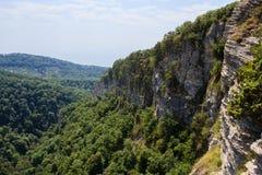 Dorp in de bergen van de Kaukasus en klip met pijnboombomen die wordt behandeld stock foto