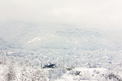 Dorp in de heuvels van bos met sneeuw worden behandeld die Stock Foto