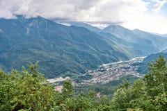 Dorp in een bergvallei onder het groene bos stock foto's
