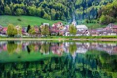 Dorp en bos in meer wordt weerspiegeld dat Royalty-vrije Stock Afbeeldingen