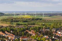 Dorp en windturbines in vlak landschap Stock Afbeelding
