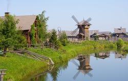 Dorp met een windmolen over rivier ? Royalty-vrije Stock Fotografie