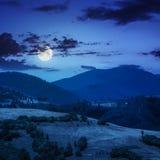 Dorp op hellingsweide dichtbij bos in berg bij nacht Royalty-vrije Stock Fotografie