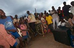 Dorpsbewoners die aan pedaal-aangedreven radio, Oeganda luisteren Stock Afbeeldingen