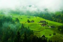 Dorpslandbouwbedrijf onder een mist in Zwitserland Royalty-vrije Stock Foto