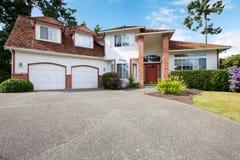 有两车库dors、红色门和砖专栏的美国大白色房子 库存图片