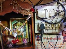 Durga Devi altar next to the electricity Board with electrical wires stock photography
