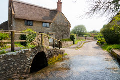Dorset village. Bridge and river ford in the Dorset village of Melbury Osmond with a cottage in the background stock image