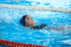 Dorso di nuoto della giovane donna in stagno Fotografie Stock Libere da Diritti
