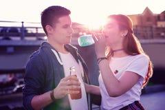 Dorstig langharig meisje die blauw sap van glasfles drinken stock fotografie