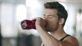 Dorstig mensen drinkwater bij sport opleiding op gymnastiektraining stock footage