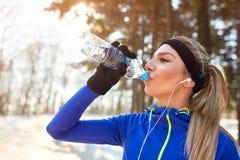 Dorstig vrouwelijk atleten drinkwater stock afbeeldingen