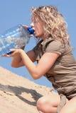 Dorstige blonde vrouw op woestijn Royalty-vrije Stock Foto