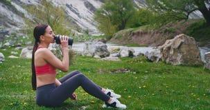 Dorstige dame na een harde training die wat water van haar sportfles drinken en van de mening genieten in het midden van stock video