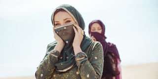 Dorstige vrouwen die in een woestijn lopen Verloren tijdens de reis royalty-vrije stock afbeeldingen