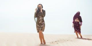Dorstige vrouwen die in een woestijn lopen Verloren tijdens de reis royalty-vrije stock afbeelding