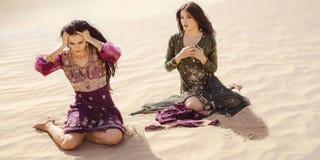 Dorstige vrouwen die in woestijn reizen Verloren in woestijn durind sandshtorm stock afbeeldingen