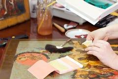 Dorure de restaurateur sur l'icône chrétienne antique Photographie stock libre de droits