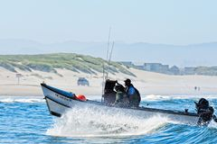 Dory Boat cuts through waves to land on beach Royalty Free Stock Photos