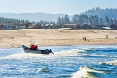 Dory boat lands on the beach at Pacific City Stock Photo
