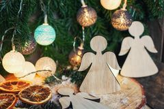 Dos ángeles de madera que cuelgan en una rama de la Navidad adornada con i Fotografía de archivo libre de regalías