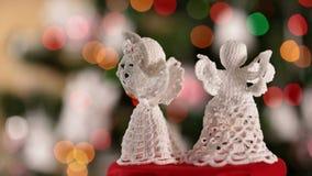 Dos ángeles de Navidad que hacen girar delante del árbol de navidad metrajes