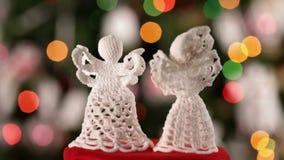 Dos ángeles hecho a ganchillos de Navidad que hacen girar delante del árbol de navidad metrajes