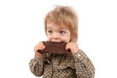 Dos años adorables del bebé que come una barra de chocolate aislado encendido Foto de archivo libre de regalías