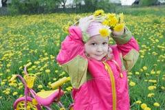 Dos años de la muchacha que pone en la guirnalda floral hecha de dientes de león amarillos vivos florecen Foto de archivo libre de regalías