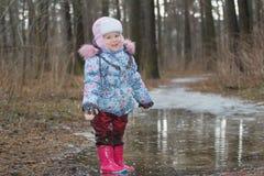 Dos años de la muchacha que se coloca en charco helado Imágenes de archivo libres de regalías