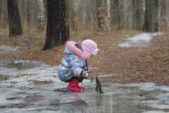 Dos años de la muchacha que se sienta en charco helado Fotos de archivo libres de regalías
