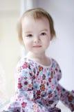 Dos años de la muchacha que se sienta por la ventana Foto de archivo libre de regalías