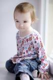 Dos años de la muchacha que se sienta por la ventana Imágenes de archivo libres de regalías