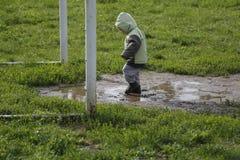Dos años de paseo del niño y el jugar en charco fangoso Imagen de archivo libre de regalías