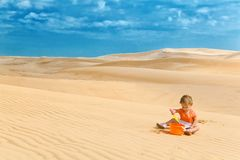 Dos años del bebé que juega en un desierto tienen gusto en una salvadera grande Imagen de archivo libre de regalías