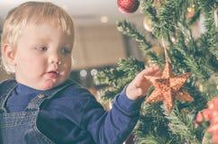 Dos años del muchacho que adorna el árbol de navidad Imagenes de archivo