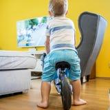 Dos años del muchacho se están sentando en su bicicleta mientras que ven la TV foto de archivo