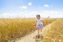 Dos años felices de la muchacha que corre en el camino del campo del centeno de la granja al aire libre en el verano Fotos de archivo libres de regalías