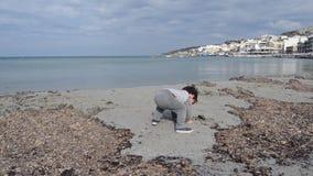 Dos años lindos del muchacho cravling en la playa que juega con alga marina y la arena almacen de video