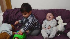 Dos años lindos del muchacho que juega con el juguete de la educación de la tortuga mientras que su hermano del bebé está mirando almacen de metraje de vídeo