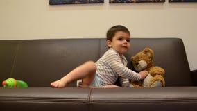 Dos a?os lindos del muchacho que ve la TV con su oso de peluche - poniendo el peluche para sentarse correctamente almacen de video