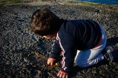 Dos años lindos del niño que juega con agua en la trayectoria de piedra foto de archivo libre de regalías
