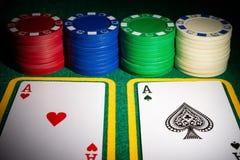Dos Ace de pókeres delante de microprocesadores de juego en la tabla del casino foto de archivo